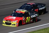 Jeff Gordon, driver of the #24 Chevrolet, and Kurt Busch, driver of the #78  Chevrolet, race during the NASCAR Sprint Cup Series 13th Annual Hollywood Casino 400 at Kansas Speedway on October 6, 2013 in Kansas City, Kansas.