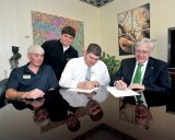 LivingShield owner Jeff Livingston, second from right, and Marshall President Stephen J. Kopp, right, sign the guidelines for the LivingShield Endowment. Looking on are, from left, Eugene Penland from LivingShield, and Livingston's son, Jeffrey.
