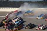 Timothy Peters, driver of the #17 , Caleb Homan, driver of the #75 , and German Quiroga, driver of the #77 , crash on track during the Camping World Truck Series Fred's 250  at Talladega Superspeedway on October 19, 2013 in Talladega, Alabama.