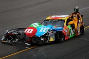 Kyle Busch, driver of the #18 M&M's Toyota, climbs from his car after an on-track incident during the NASCAR Sprint Cup Series 13th Annual Hollywood Casino 400 at Kansas Speedway on October 6, 2013 in Kansas City, Kansas.