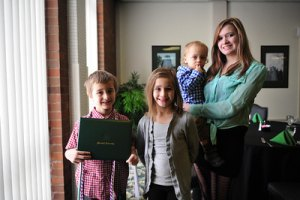 Owen Moul&#039;s children pose with their dad&#039;s diploma they received today from Marshall University. From left to right are Owen Jr., 7, holding the diploma; Sierra, 8, Zane, 1, and Sydney, 14. Photo by Liu Yang/Marshall University.