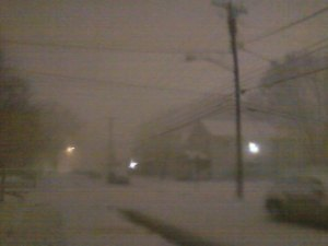 Snow barrels down in Huntington on a dark street missing a light.