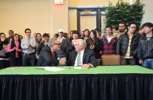 Andrew Colin, left, chairman of INTO University Partnerships, and Marshall President Dr. Stephen J. Kopp shake hands after signing an agreement today.