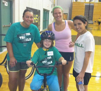 Marshall staff member Megan Archer (left), stands with COHP student Amy Bowen (center), and camp volunteer Brianna (right) as they help 10-year- old Sarah Brown learn to ride a bike during the 2013 Lose the Training Wheels Camp