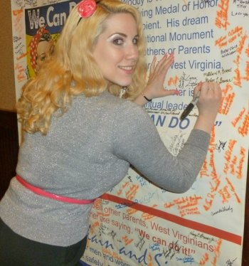 Model Elsa Littlepage signs Rosie part of the permanent Rosie exhibit in 2013 at Pullman Plaza Hotel.