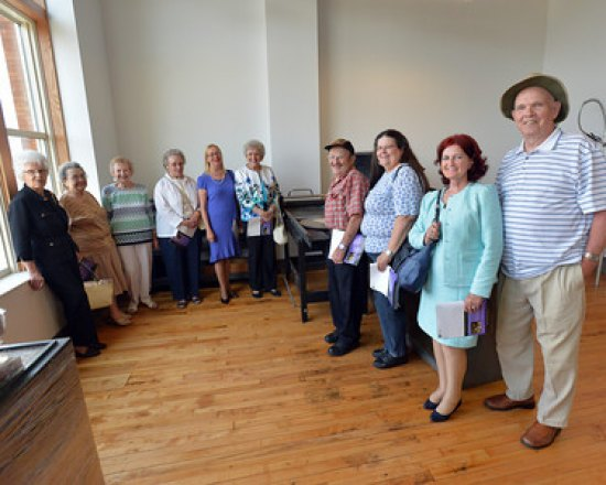 Fern Fitzpatrick, Lottie Woody, Elsie Singleton, Lula Cremeans; Donna Rawley; Opal Blake; Yvonne and Virgil Newman; and Jerry and Shirley Blake, the former Anderson-Newcomb employees who toured the building, stand with an early 1900s printing press.