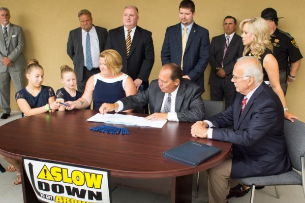 Gov Earl Ray Tomblin and Tiffany Tabler hand a pen to Jewelia Tabler (left) as Annaliese Tabler watches