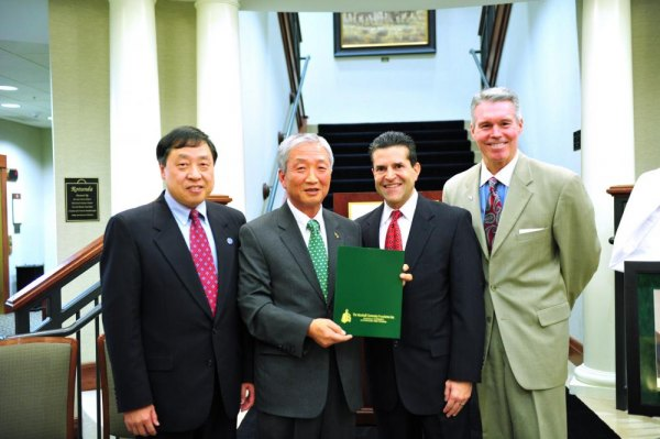 From left, Dr. Haiyang Chen, Dr. Chong Kim, Norman Mosrie, and Lance West, pose with a copy of the guidelines for the Kim scholarship.