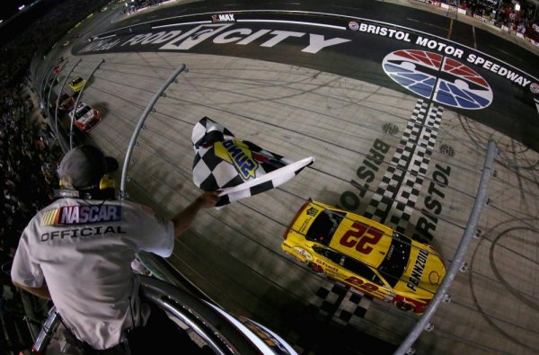 Joey Logano, driver of the #22 Shell Pennzoil Ford, takes the checkered flag to win the NASCAR Sprint Cup Series Irwin Tools Night Race at Bristol Motor Speedway on August 23, 2014 in Bristol, Tennessee.